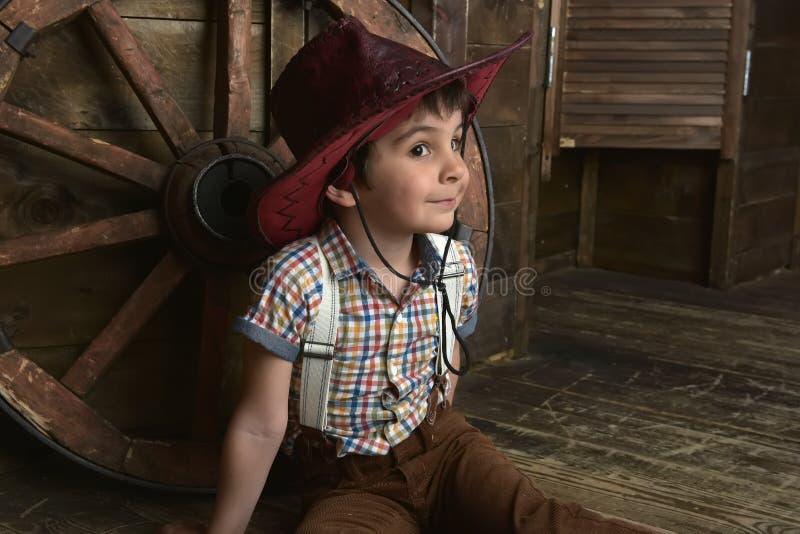Weinig jongen kleedde zich in cowboyzitting royalty-vrije stock fotografie