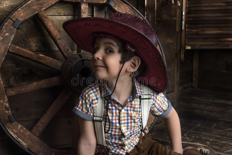 Weinig jongen kleedde zich in cowboyzitting royalty-vrije stock afbeeldingen