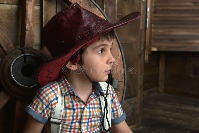Weinig jongen kleedde zich in cowboyzitting royalty-vrije stock afbeelding