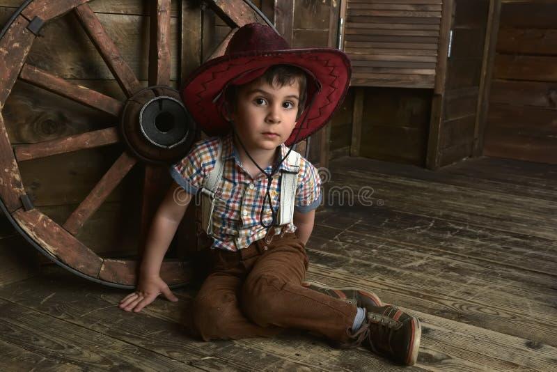 Weinig jongen kleedde zich in cowboyzitting stock foto's