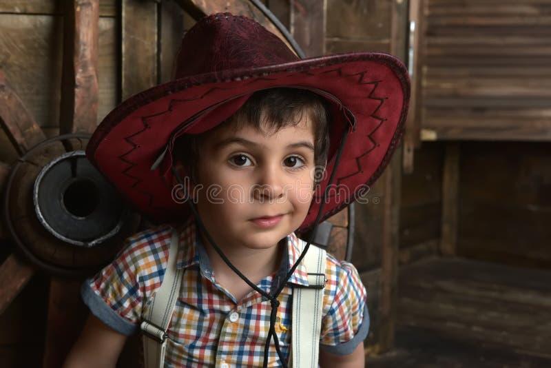 Weinig jongen kleedde zich in cowboyzitting royalty-vrije stock foto