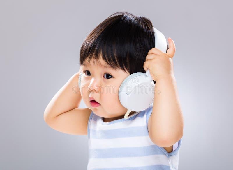 Weinig jongen luistert aan de muziek en de holding de hoofdtelefoon royalty-vrije stock afbeeldingen