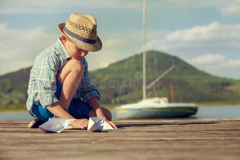 Weinig jongen maakt document boten zittend op de houten pijler stock afbeeldingen