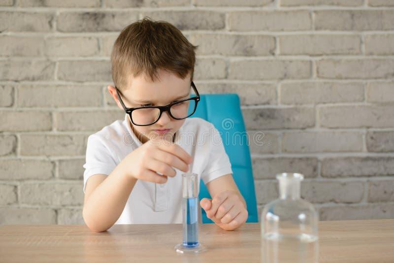 Weinig jongen maakt een binnen chemische test met water royalty-vrije stock foto