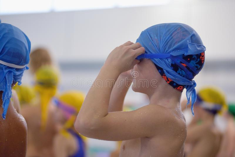 Weinig jongen maakt zijn zwemmende beschermende brillen in pool recht stock afbeelding