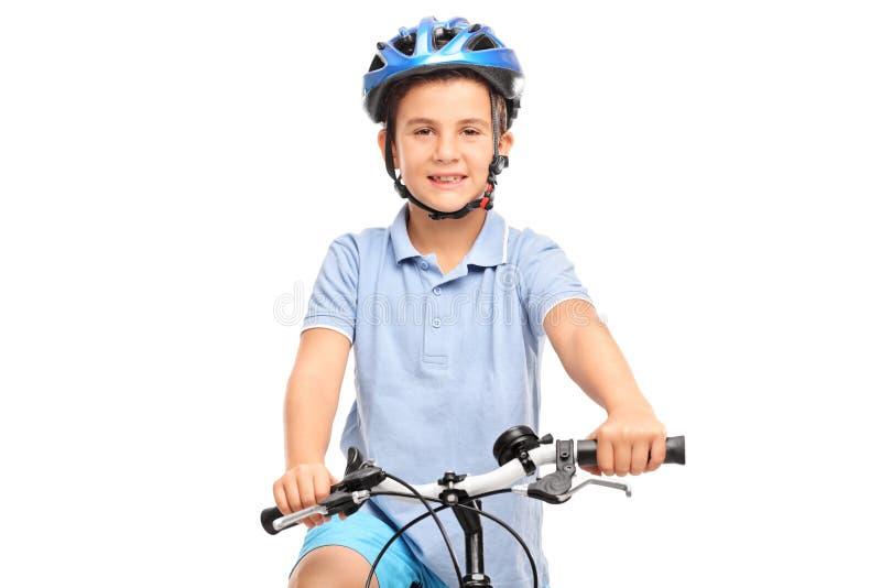 Weinig jongen met blauwhelm het stellen op een fiets royalty-vrije stock fotografie