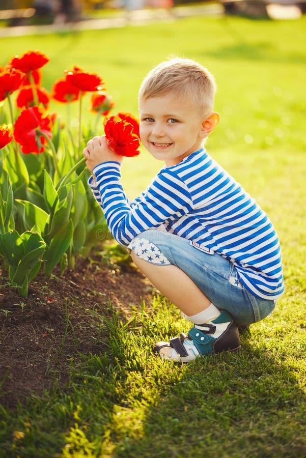 Weinig jongen met bloemen stock fotografie