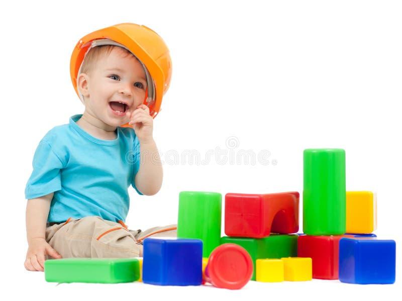 Weinig jongen met bouwvakker en bouwstenen stock fotografie