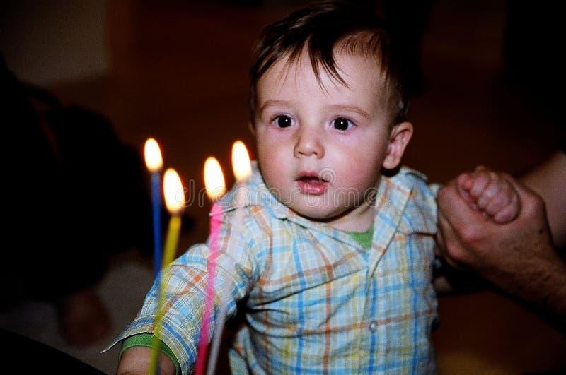 weinig jongen met de kaarsen van de verjaardagscake stock foto