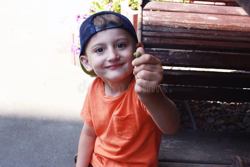 Weinig jongen met een eikel in zijn hand dichtbij de lijst aangaande de straat stock foto