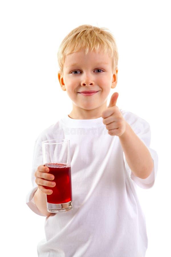 Weinig jongen met een glas sap royalty-vrije stock afbeelding