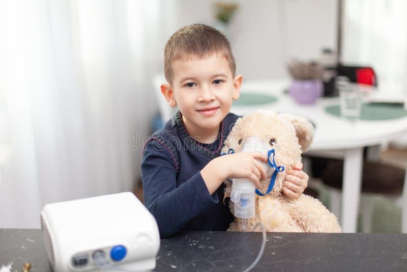 Weinig jongen met een inhaleertoestelverstuiver maakt de procedure aan zijn stuk speelgoed, konijntje Inhalatie thuis voor hoestg royalty-vrije stock fotografie