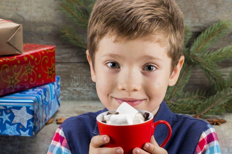 Weinig jongen met een kop van hete chocolade met heemst op royalty-vrije stock foto's