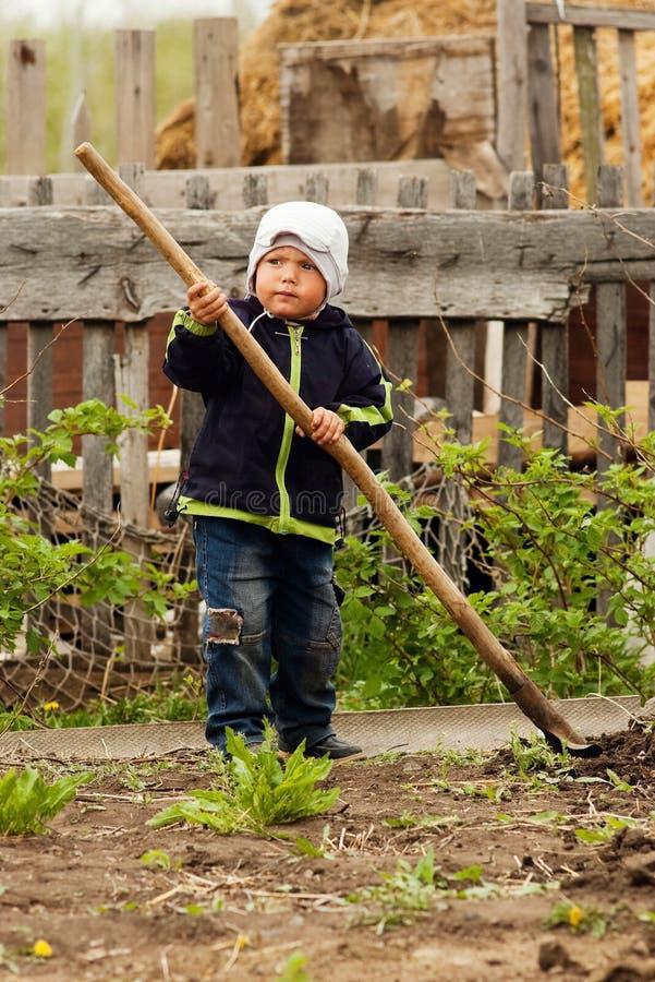 Weinig jongen met een spade in de tuin Het leven van het dorp royalty-vrije stock foto