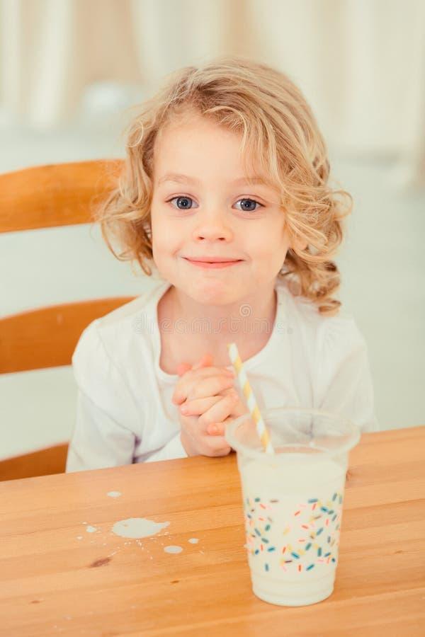 Weinig jongen met gemorste melk stock afbeelding