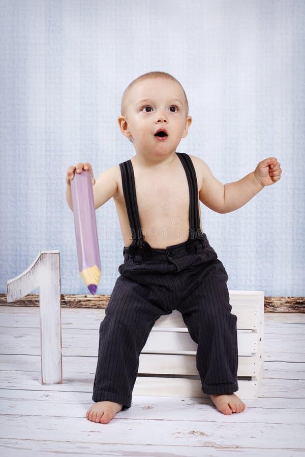 Weinig jongen met groot kleurpotlood stock foto