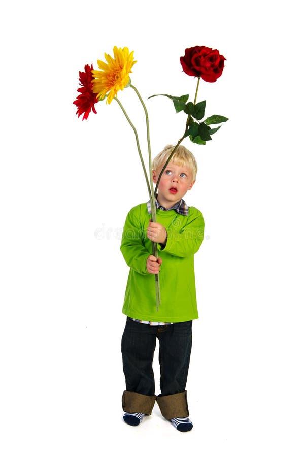 Weinig jongen met grote bloemen royalty-vrije stock afbeeldingen