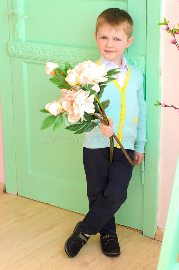 Weinig jongen met grote witte bloemen binnen stock afbeelding