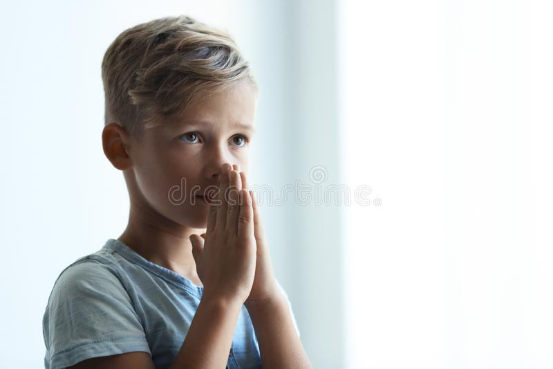 Weinig jongen met handen clasped samen voor gebed op lichte achtergrond stock foto's