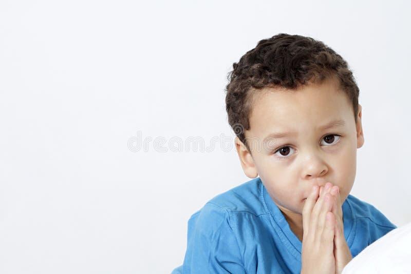 Weinig jongen met handen die samen bidden stock foto