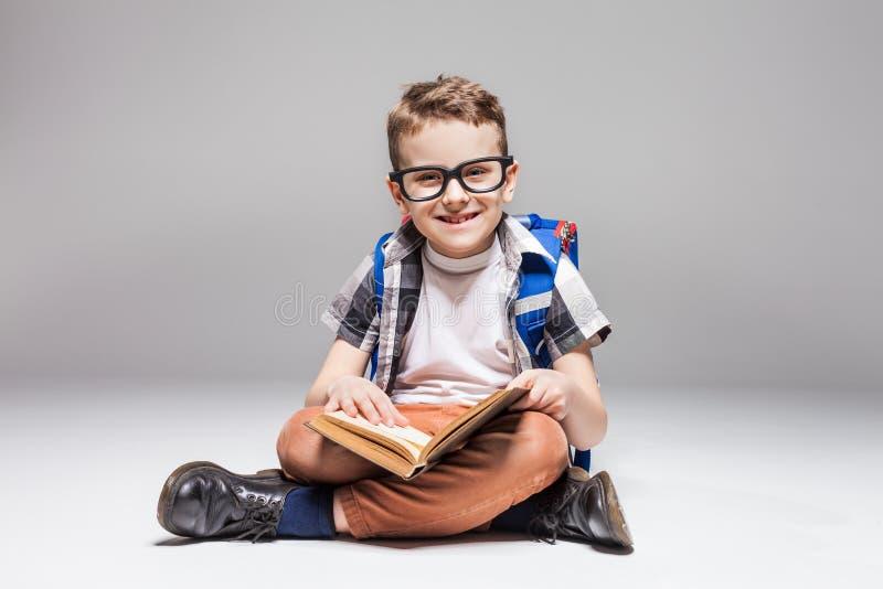Weinig jongen met het boek van de rugzaklezing in yoga stelt stock foto's