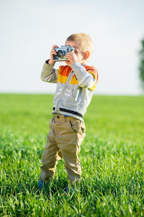 Weinig jongen met het oude camera openlucht schieten royalty-vrije stock foto's