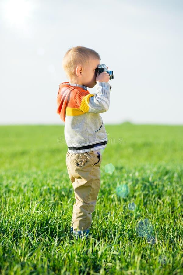 Weinig jongen met het oude camera openlucht schieten royalty-vrije stock fotografie