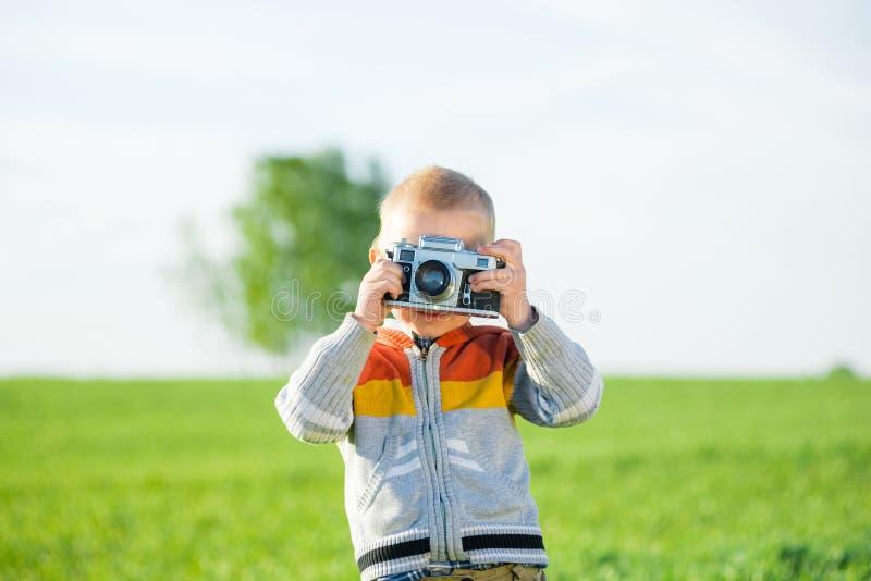 Weinig jongen met het oude camera openlucht schieten stock foto's