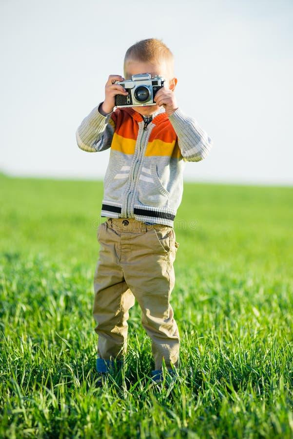 Weinig jongen met het oude camera openlucht schieten royalty-vrije stock afbeelding