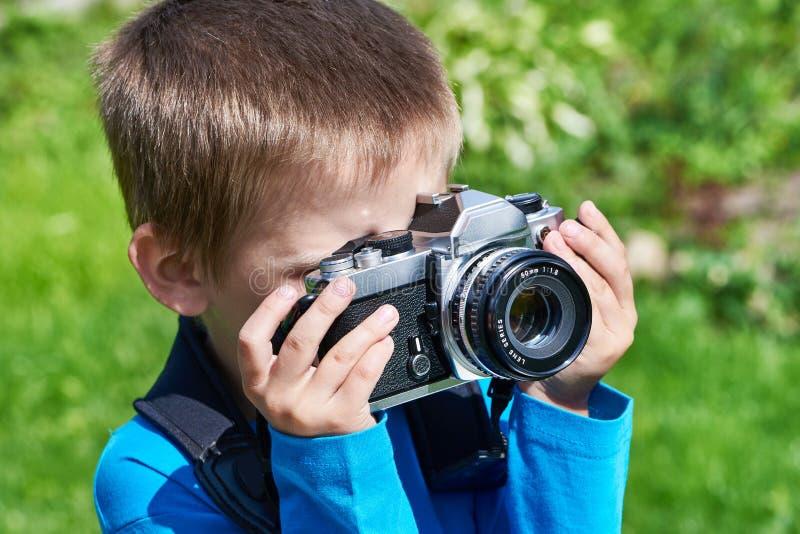 Weinig jongen met het retro SLR-camera schieten stock fotografie