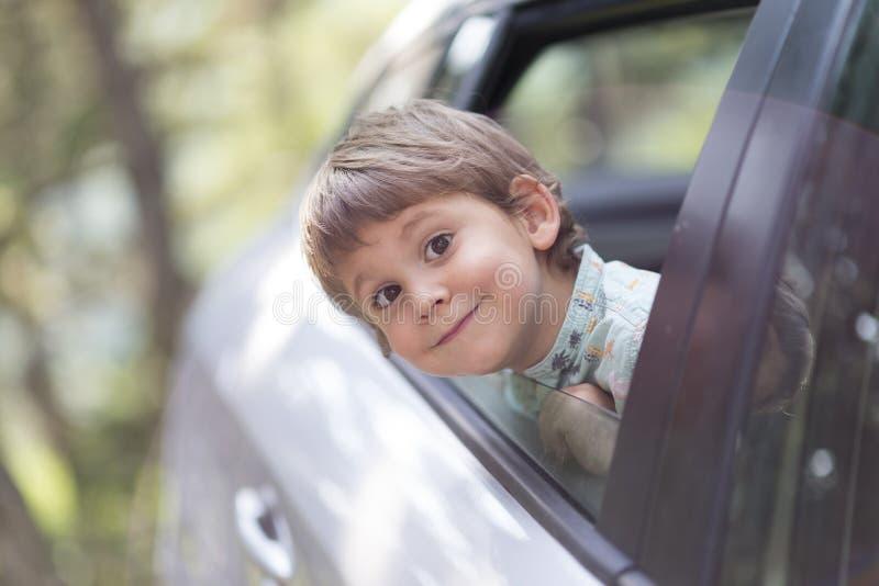 Weinig jongen met hoofd leunde door het open venster van een auto stock foto's