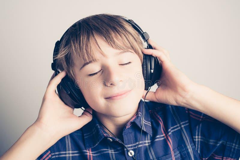 Weinig jongen met hoofdtelefoon het luisteren muziek royalty-vrije stock foto's