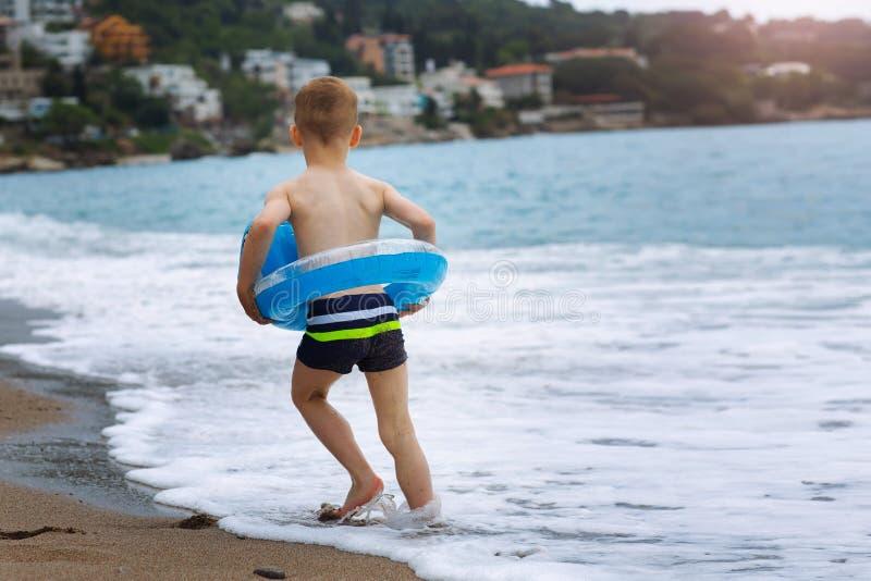 Weinig jongen met kleurrijke rubberring op de zomerstrand stock afbeelding