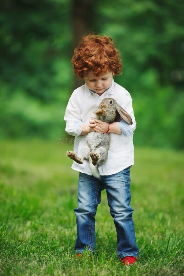Weinig jongen met konijn op gras stock foto's