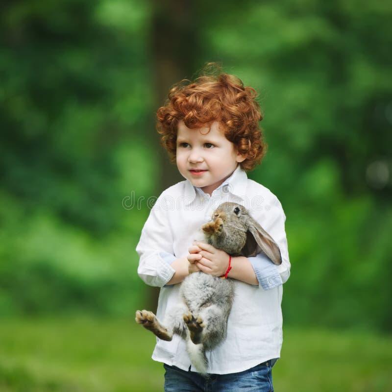 Weinig jongen met konijn op gras royalty-vrije stock afbeeldingen