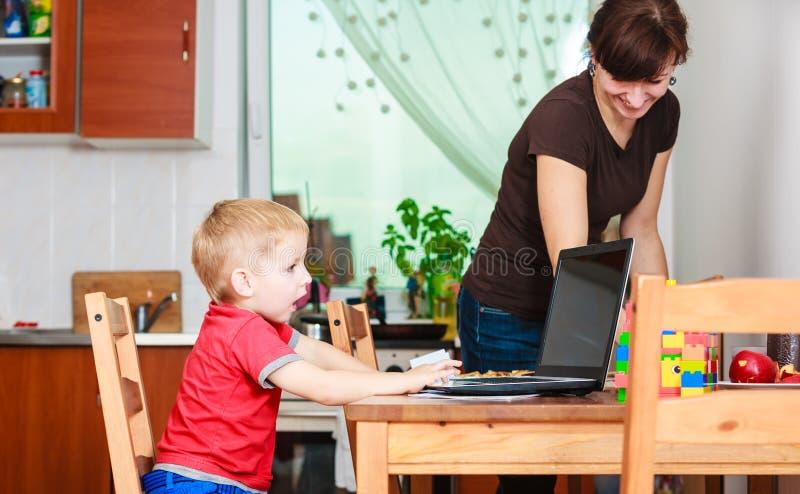 Weinig jongen met laptop en moeder het schoonmaken stock afbeeldingen