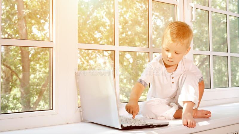 Weinig jongen met laptop op venstervensterbank royalty-vrije stock fotografie