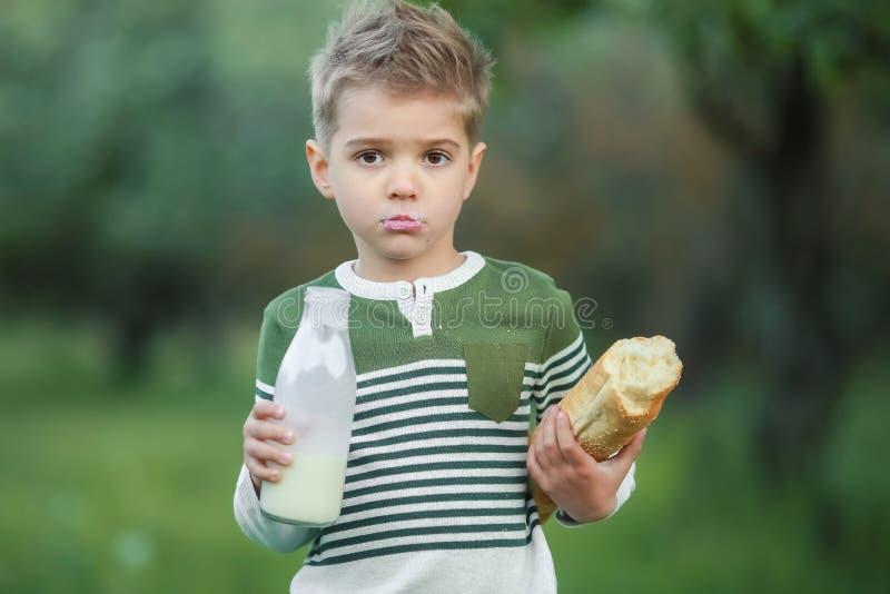 Weinig jongen met meisje drinkt melk en eet een brood van brood op een hooiberg in een dorp bij zonsondergang stock foto's