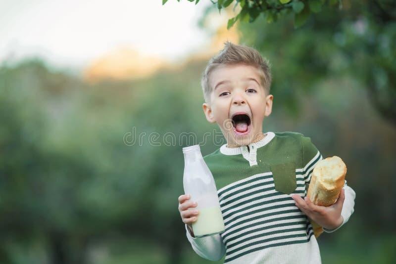 Weinig jongen met meisje drinkt melk en eet een brood van brood op een hooiberg in een dorp bij zonsondergang royalty-vrije stock afbeeldingen