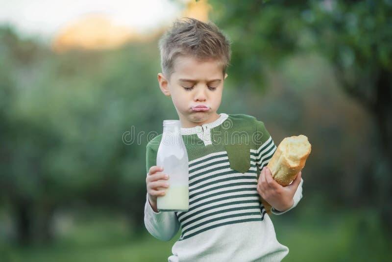 Weinig jongen met meisje drinkt melk en eet een brood van brood op een hooiberg in een dorp bij zonsondergang royalty-vrije stock foto's