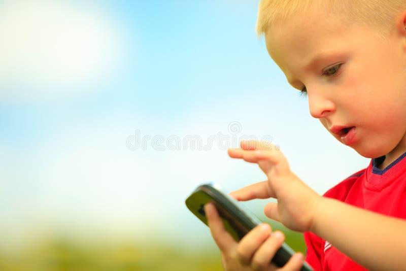 Weinig jongen met mobiele telefoon openlucht Technologiegeneratie royalty-vrije stock afbeeldingen