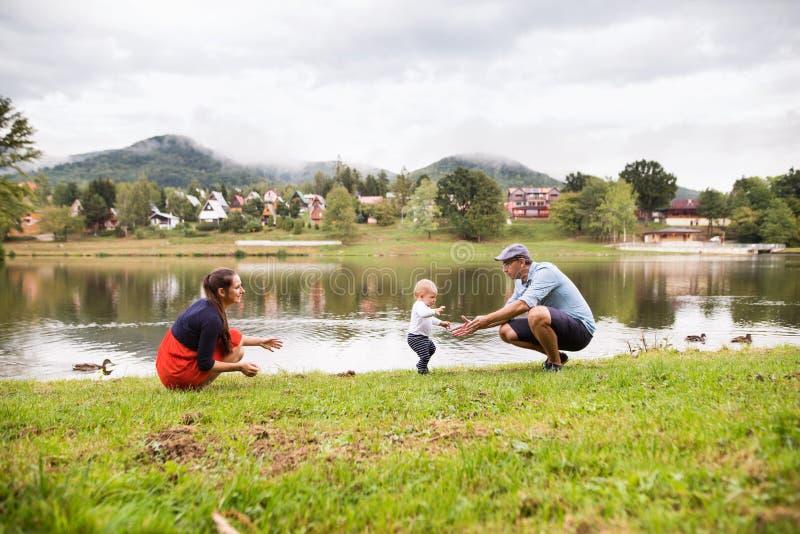 Weinig jongen met ouders die eerste stappen maken stock afbeelding