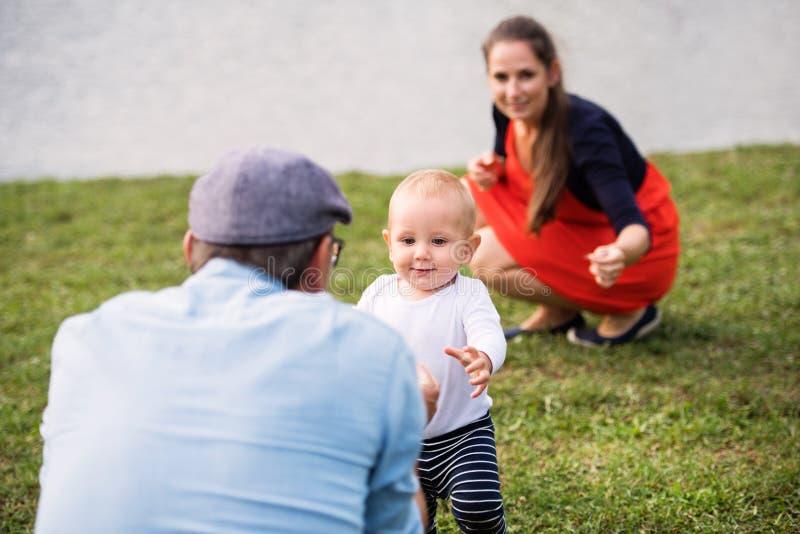 Weinig jongen met ouders die eerste stappen maken stock foto