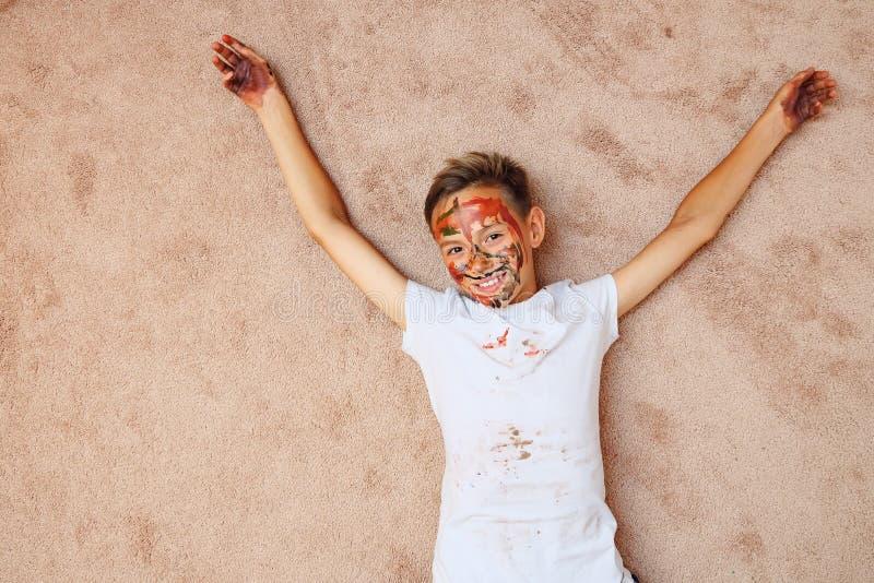 Weinig jongen met palmen en gezicht in heldere kleurrijke verven die camera bekijken die op vloer liggen stock afbeeldingen