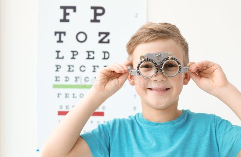 Weinig jongen met proefkader dichtbij ooggrafiek stock fotografie