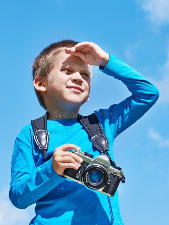 Weinig jongen met retro camera op hemel onderzoekt afstand stock foto's