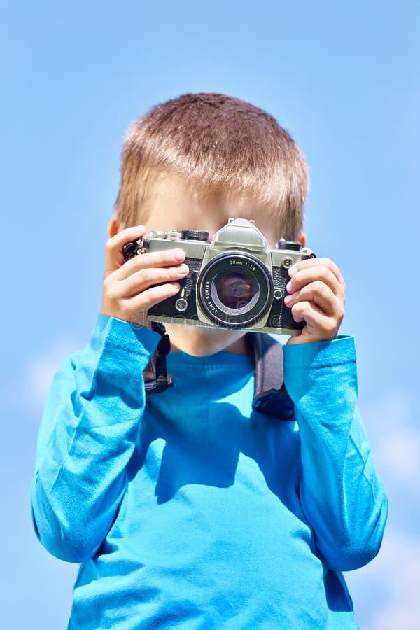 Weinig jongen met retro SLR-camera op blauwe hemel stock foto
