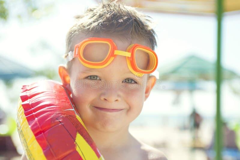 Weinig jongen met rubberring die zich op het strand in de dagtijd bevinden Leuk weinig jongen met opblaasbare ring op het strand royalty-vrije stock fotografie