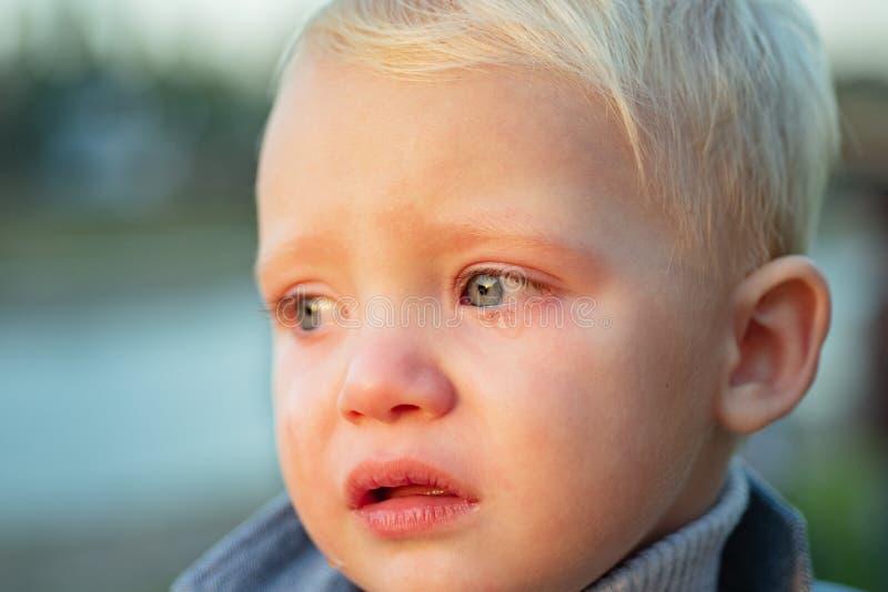 Weinig jongen met scheuren dichte omhooggaand defocused achtergrond Emotionele droevige baby Peuter het droevige gezicht schreeuw royalty-vrije stock afbeelding