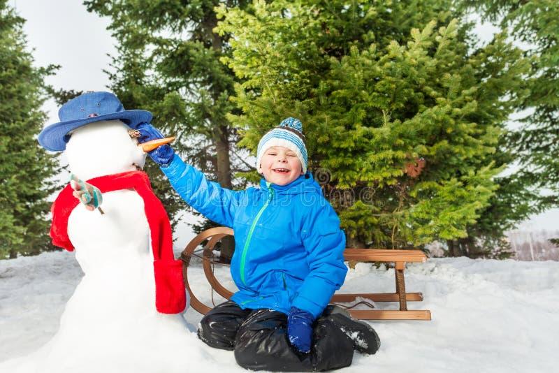 Weinig jongen met slee maakt sneeuwman in park stock afbeelding
